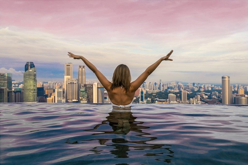 Woman in the pool with city view