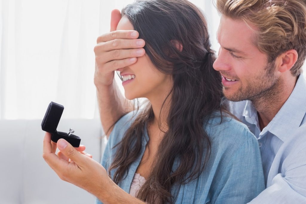 Man covering his girlfriend's eyes while proposing