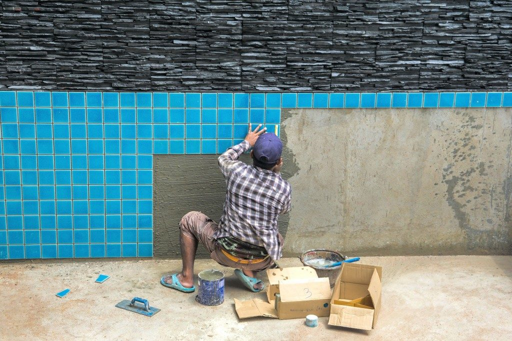 man installing tiles for swiming pool