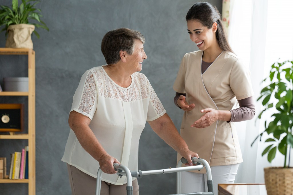 elderly woman with walker being assisted by nurse