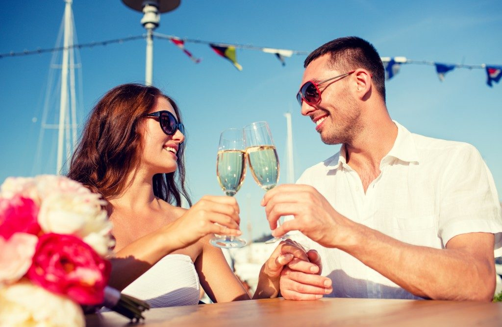 smiling couple wearing sunglasses drinking champagne