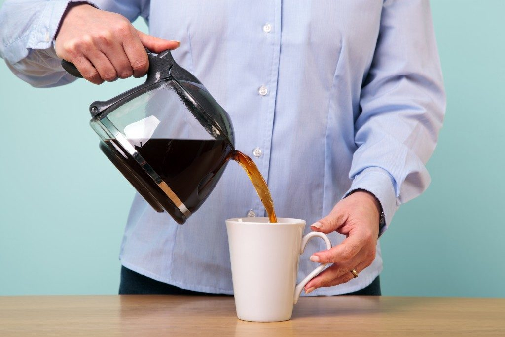 person pouring coffe in the mug