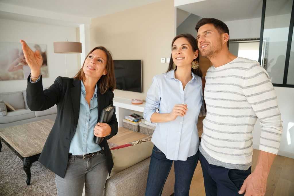 couple looking at a brand new house with realtor