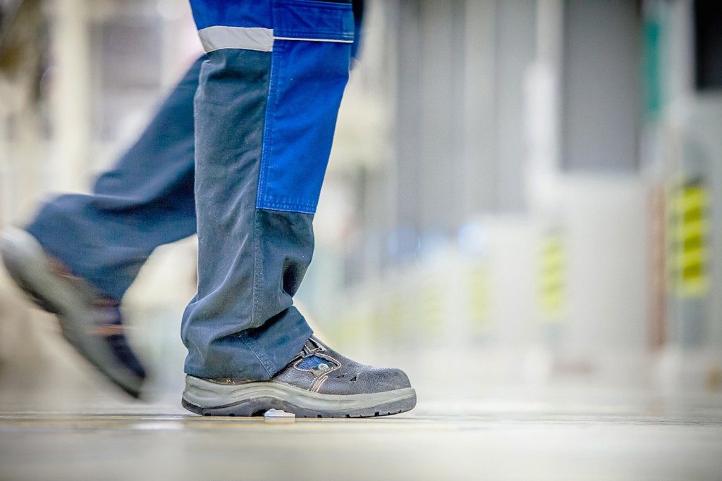 Man walking with safety shoes inside a facility