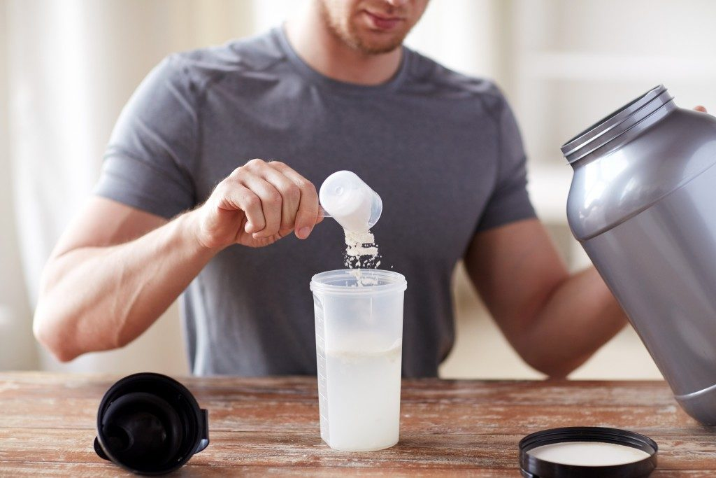 close up of man with jar and bottle preparing protein shake