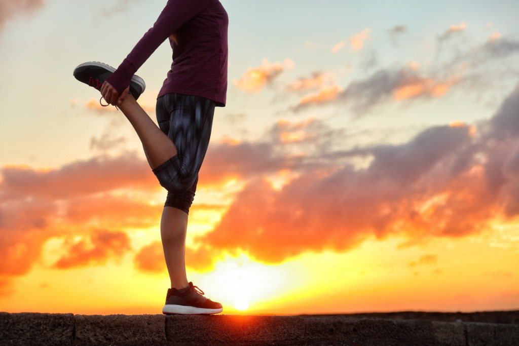 woman stretching leg muscle preparing for sunset trail run in outdoor summer