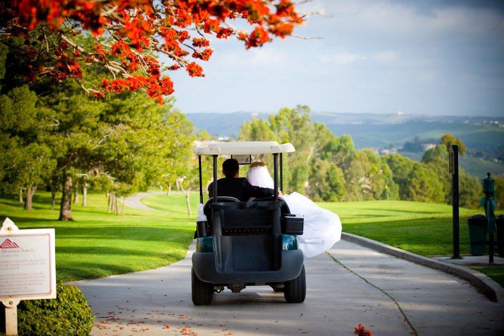 newlyweds riding a golf cart