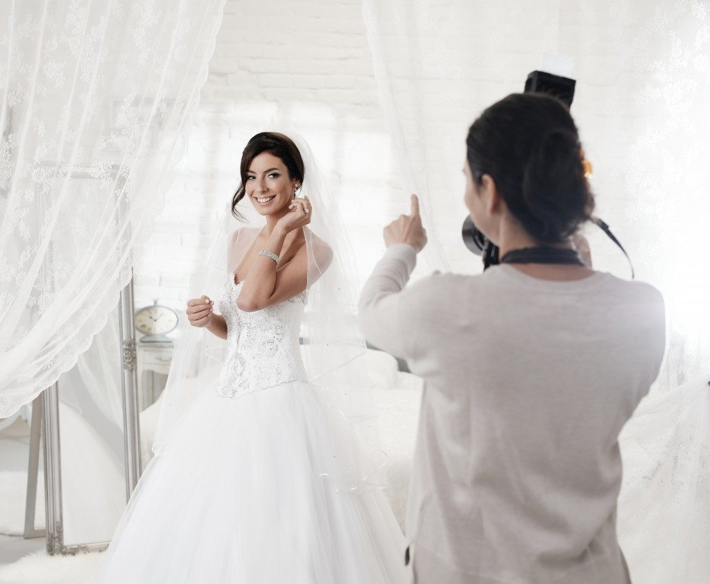 photographer photographing beautiful happy bride