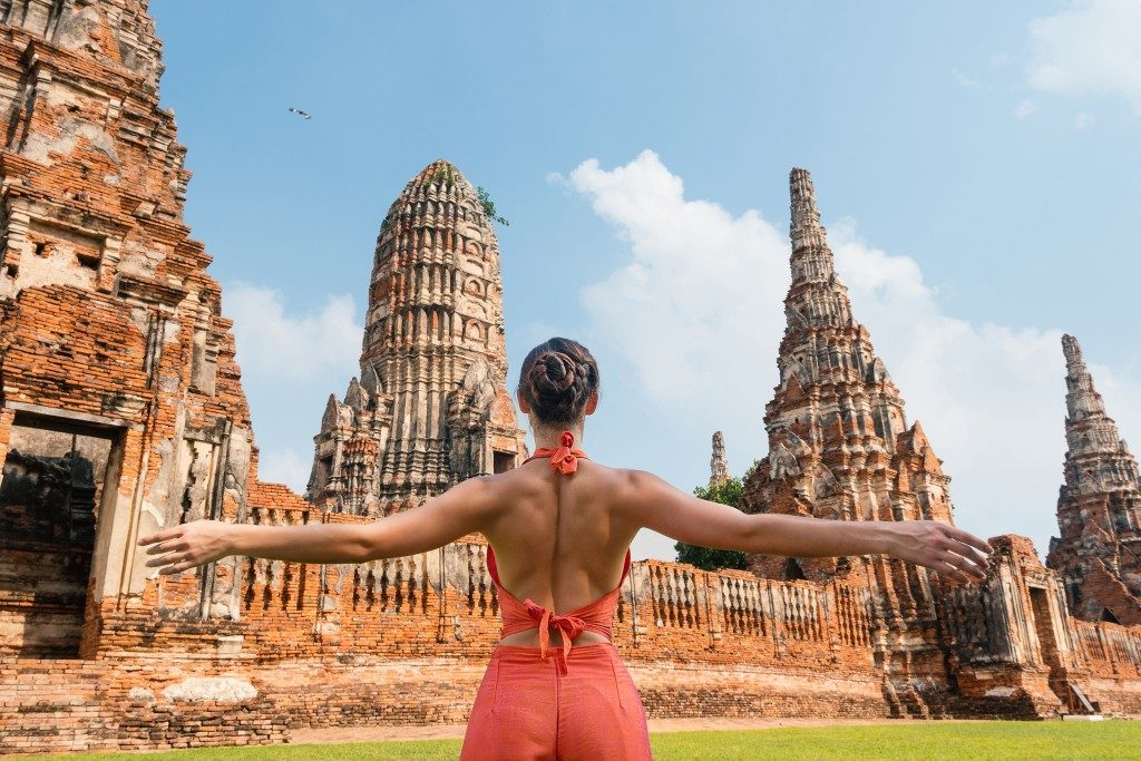 Woman looking at the view of old temples in Bangkok Thailand