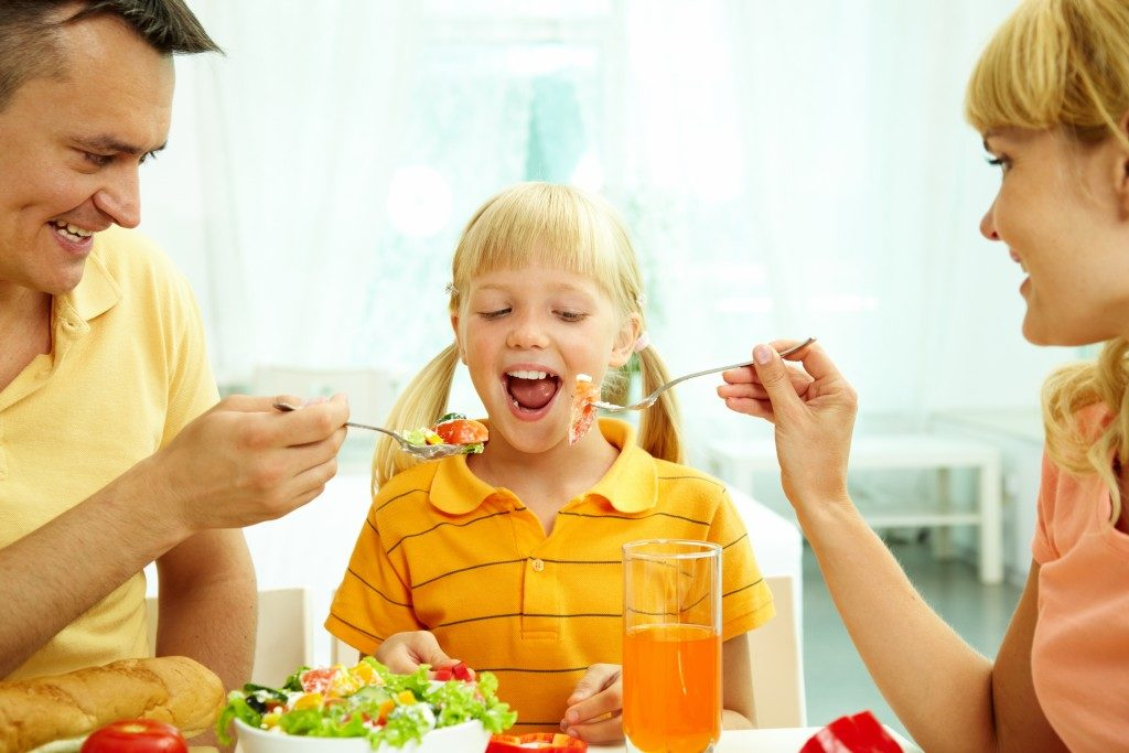 Portrait of happy parents feeding their daughter with salad in the kitchen