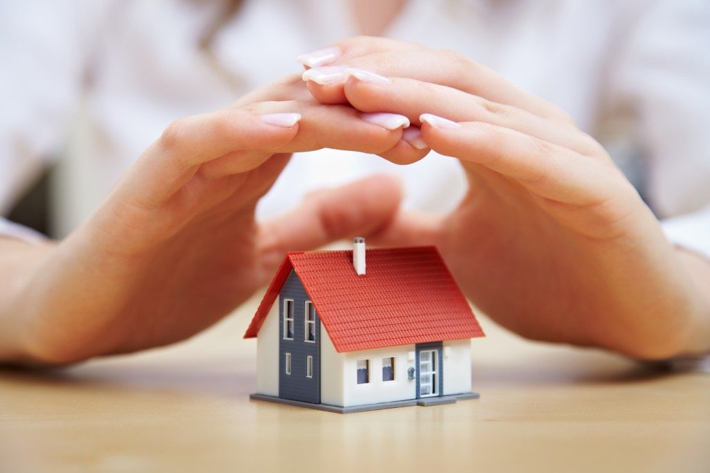 woman's hand over a tiny model of a house