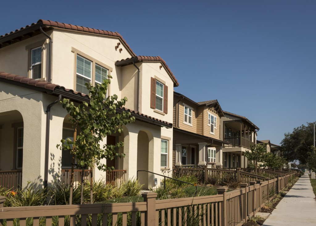 A row of new homes with fenced yards along a sidewalk