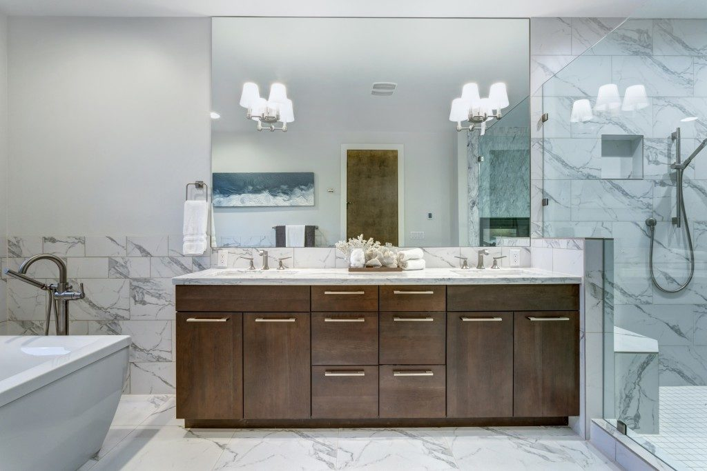 Bathroom with white marble tiles and big vanity sink and mirror