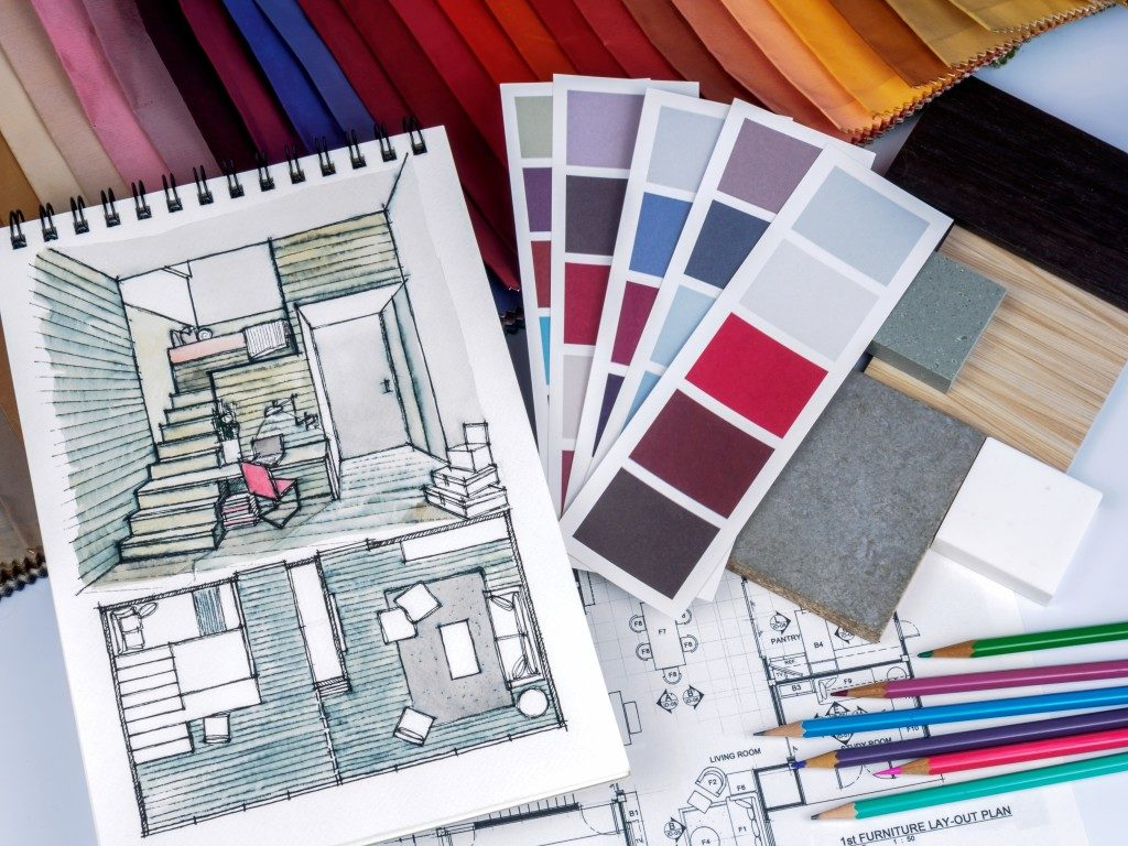 sketch of house remodel, swatches of color, blueprint and color pencils