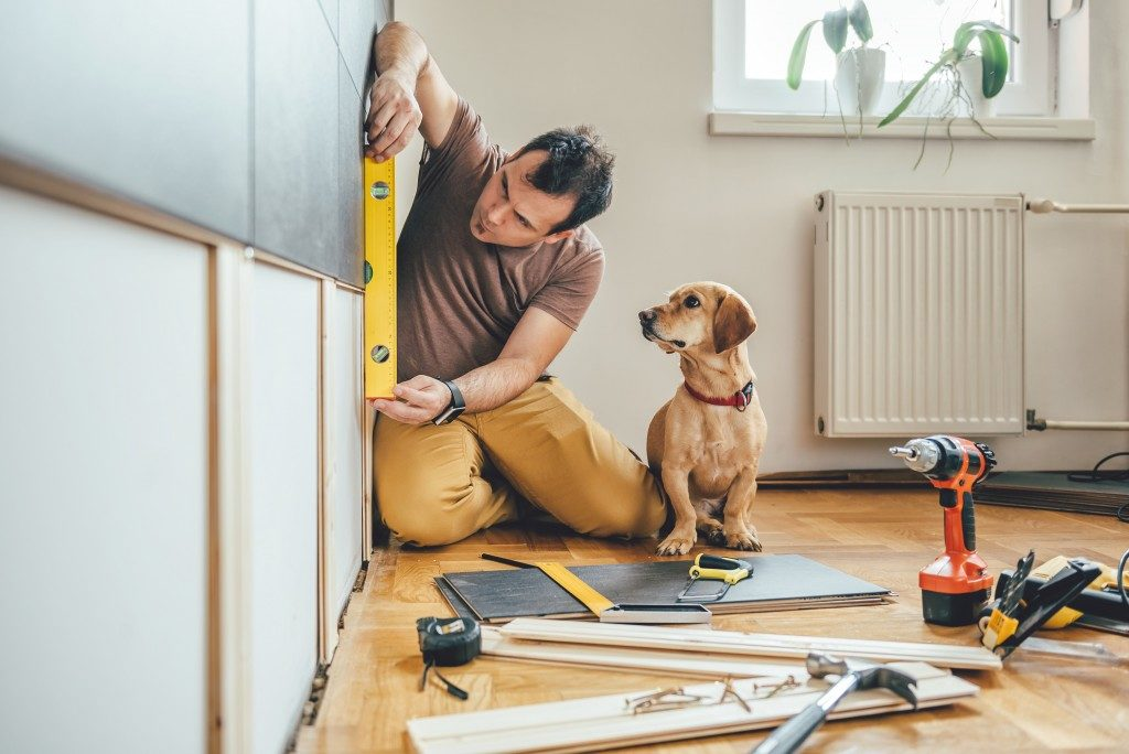 man measuring wood on wall while his dog watches