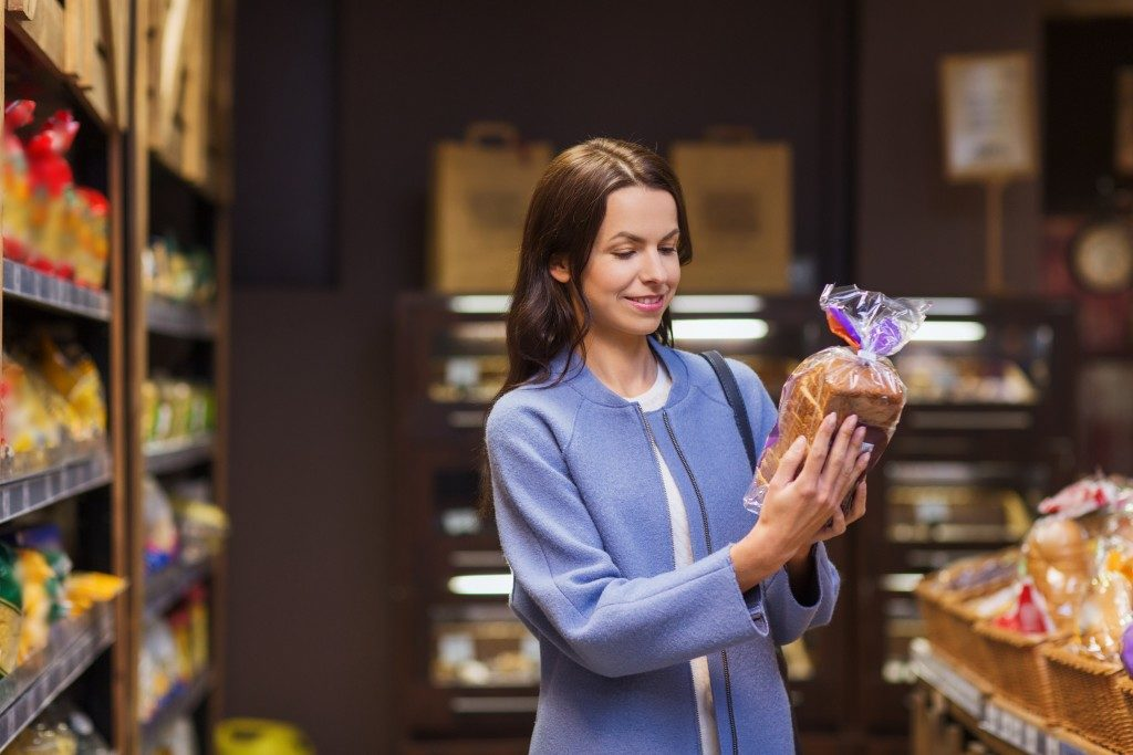 Woman choosing and reading label on bread in market