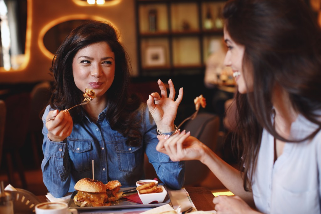 woman enjoying food at the restaurant with her friend